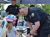Photo of an officer talking to a girl at the town's bike night event.