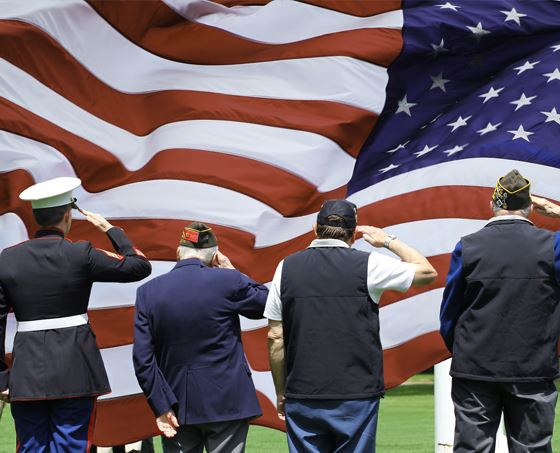 Veterans salute a large American flag